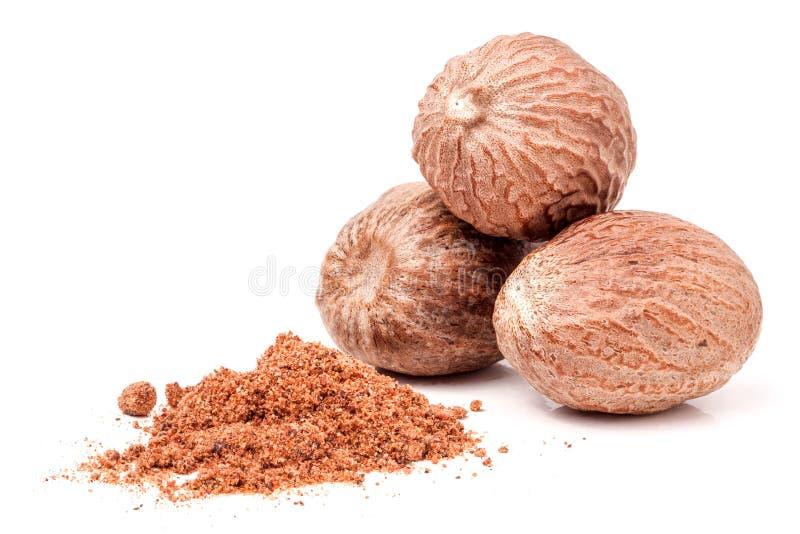 Three nutmeg whole and powder isolated on white background.  stock image