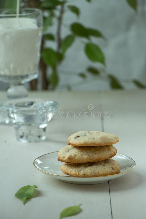Three Oatmeal cookies at porcelain plate and wooden background, with glass of milk light and white photography in a rustic style. Oatmeal cookies with a glass of royalty free stock images