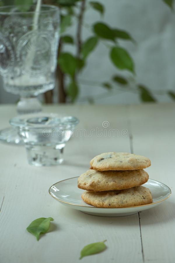 Three Oatmeal cookies at porcelain plate and wooden background, with glass of milk light and white photography in a rustic style. Oatmeal cookies with a glass of stock image