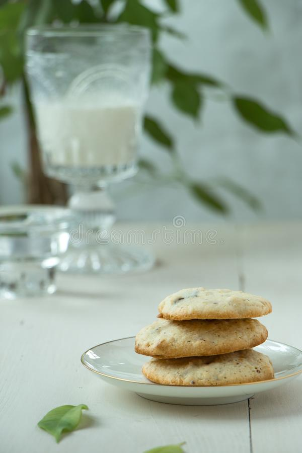 Three Oatmeal cookies at porcelain plate and wooden background, with glass of milk light and white photography in a rustic style. Oatmeal cookies with a glass of stock photo