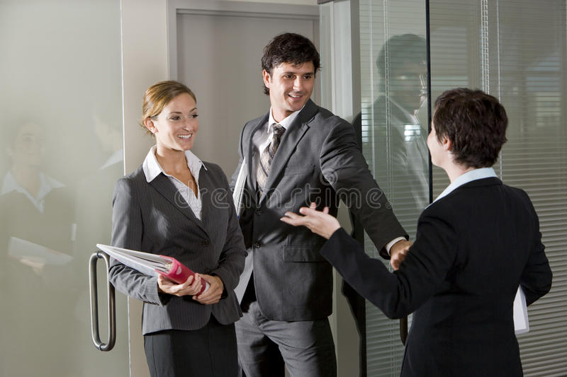 Three office workers chatting at door of boardroom. Three office workers chatting at open door of boardroom stock photography