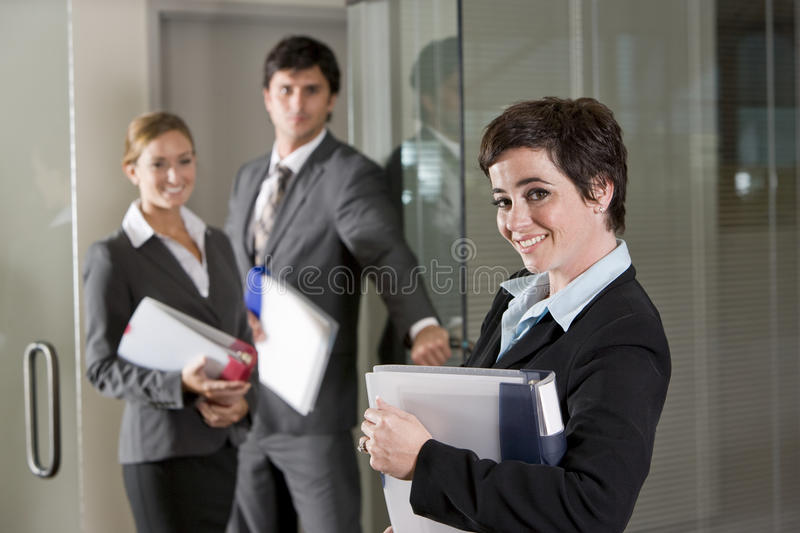 Three office workers at door of boardroom. Focus on woman in foreground stock images