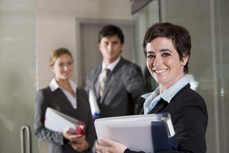 Three office workers at door of boardroom. Focus on woman in foreground royalty free stock photos