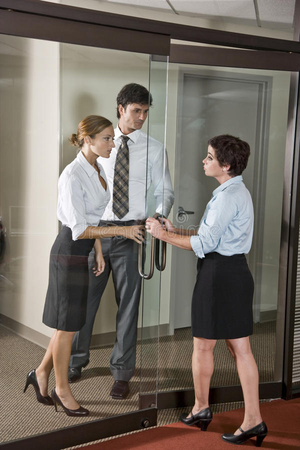 Three office workers at door of boardroom. One inside, two outside royalty free stock photography