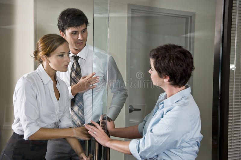 Three office workers at door of boardroom. Three office workers at glass door of boardroom, one inside, two outside stock photo