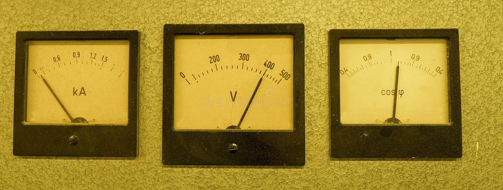 Three old analog instruments - Power factor meter, voltmeter and ampere meter isolated on grey background royalty free stock images