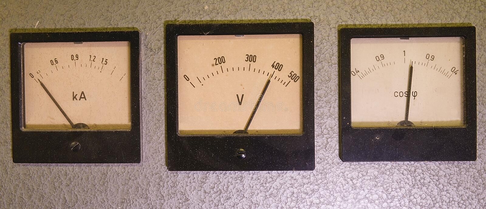 Three old analog instruments - Power factor meter, voltmeter and ampere meter isolated on grey background stock photo