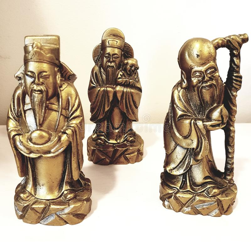 Three old asian guru figures. In gold color stock image
