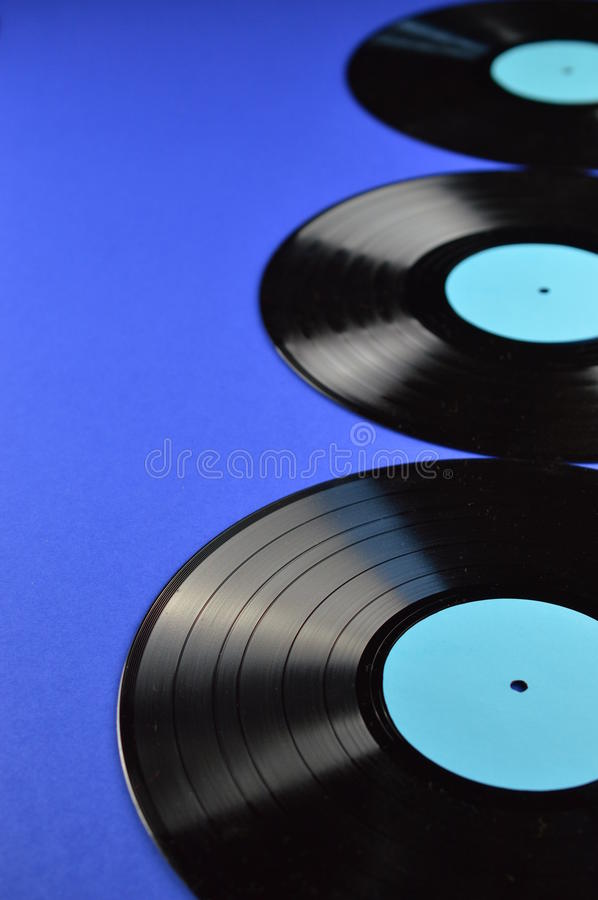 Three old black vinyl records on blue background stock image