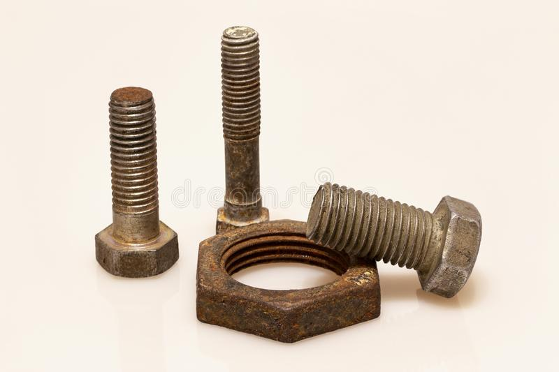 Three old bolts and a rusty nut stock images