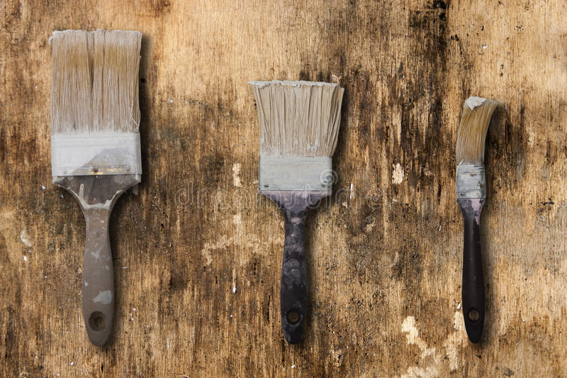 Three old brushes on a surface of old and dirty royalty free stock image