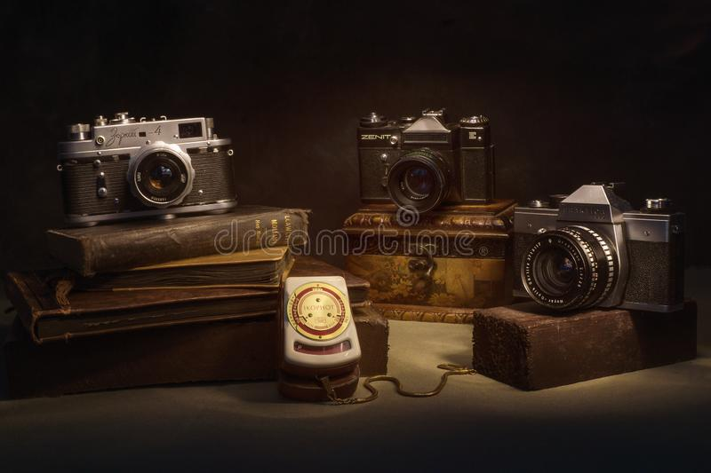 Old legacy cameras. Three old cameras, an exposure meter stock photography
