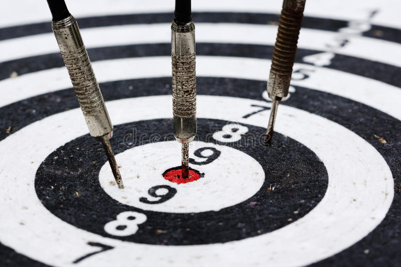 Three old darts hitting the target stock images