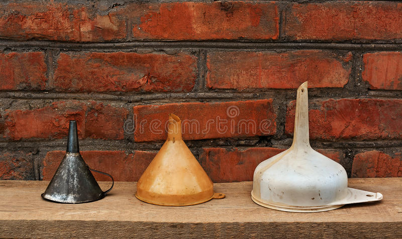 Three old fashioned funnels from metal and plastic on rustic woo stock images