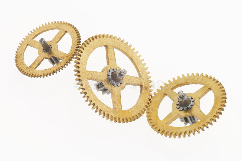 Three old golden cogwheels. Three old gold-coloured little cogwheels are connected royalty free stock images