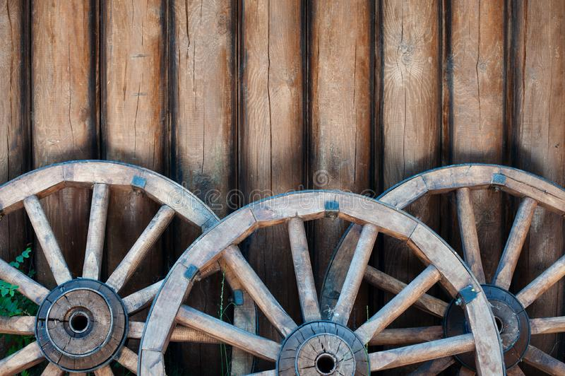 Three old wooden wheels from carts on a log wall background stock photos