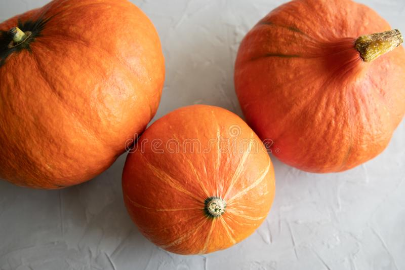Three orange Hokkaido pumpkins of different sizes lying on a concrete gray background. Autumn stock images