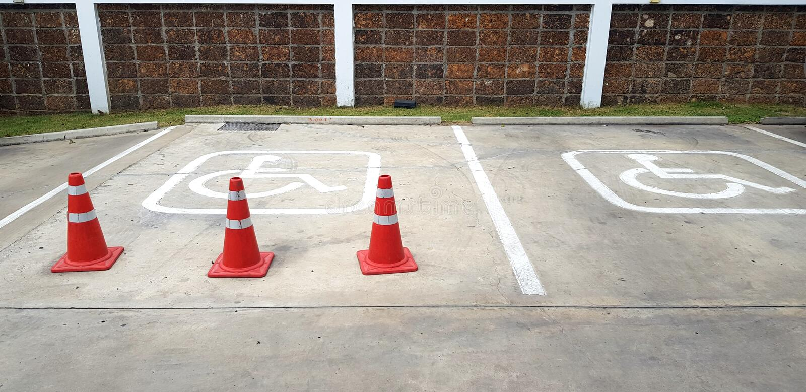 Three orange traffic cone on street for reservation parking of disabled people. With brown brick wall background - Symbol, Restrict area and Service royalty free stock photography