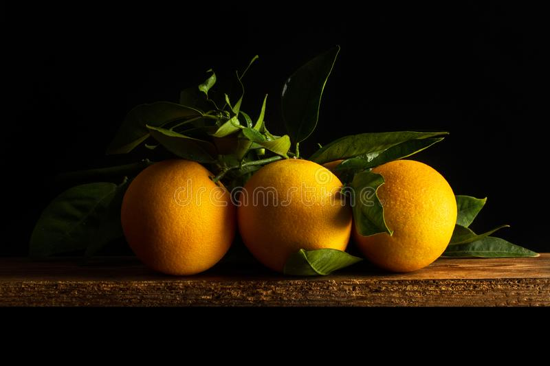 Three oranges with leaves on a wooden table royalty free stock photo