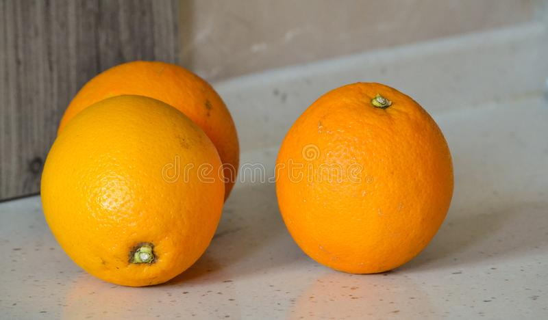 Three oranges on a stone table closeup royalty free stock image