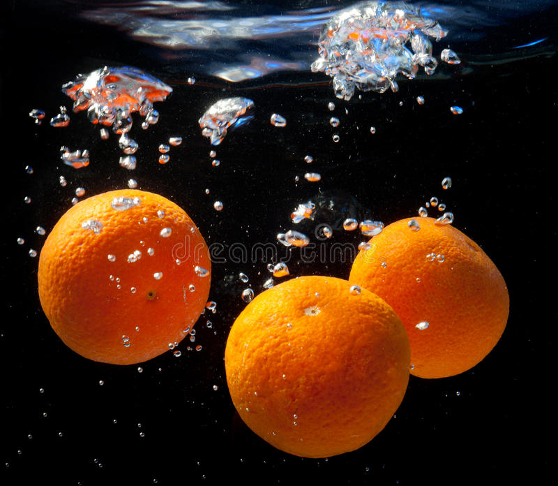 Three oranges in water. With bubbles. On a black background stock image