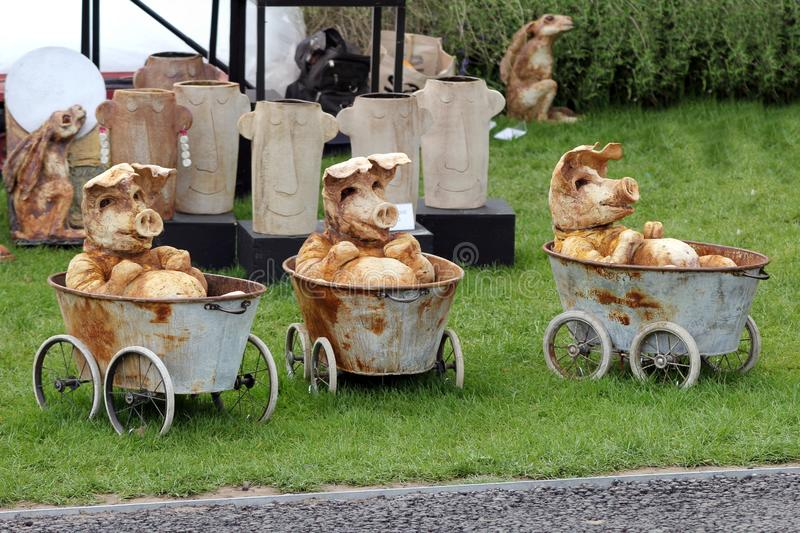 Three ornamental pottery pigs in bathtubs on wheels, at a craft. Wisley, Surrey, UK - April 30 2017: Three ornamental pottery pigs in bathtubs on wheels, at a stock photography