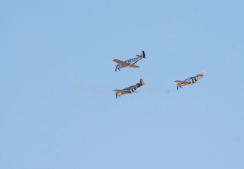 Three P-51 Mustang fighter planes fly in formation
