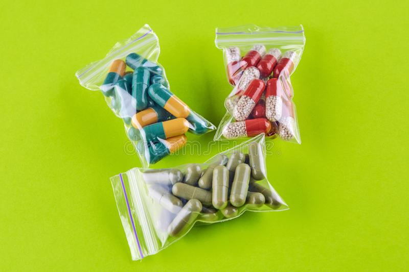 Three packs with colorful pills on green background.  stock photo