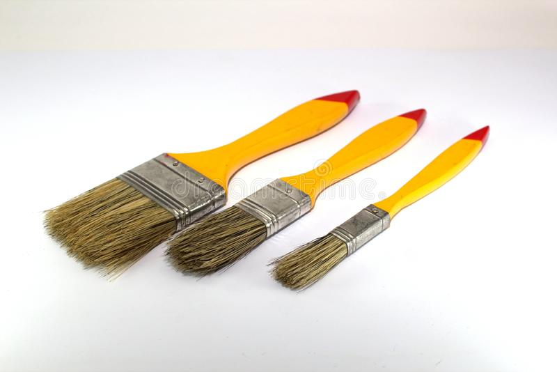 Three paint brushes with a width of 1 inch, 2 inches and 0.5 inches with yellow handles on a white background. Close-up royalty free stock photo