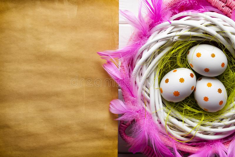 Three painted Easter eggs in the nest and blank paper sheet royalty free stock photos