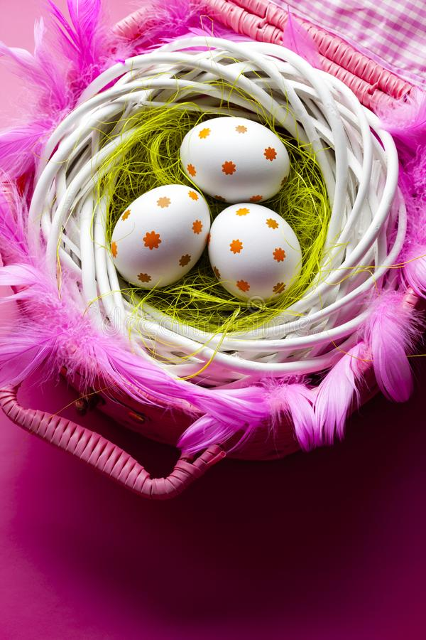 Three painted Easter eggs in the nest and pink basket stock photo