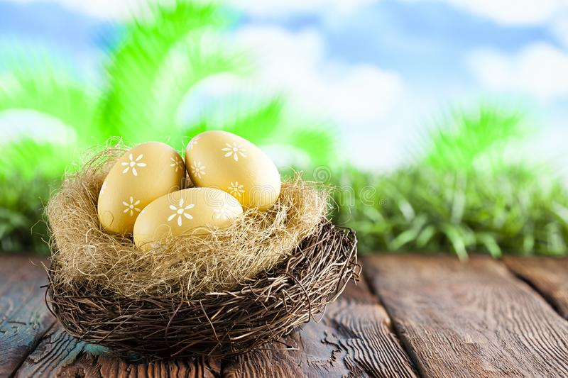 Three painted Easter eggs in the nest on table and nature background royalty free stock photography