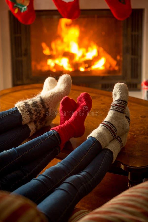 Three pair of feet in socks warming at burning fireplace at house. Three pair of feet in woolen socks warming at burning fireplace at house royalty free stock photos