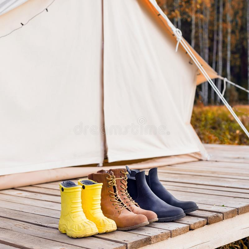 Three pair of shoes near a canvas tent stock photos