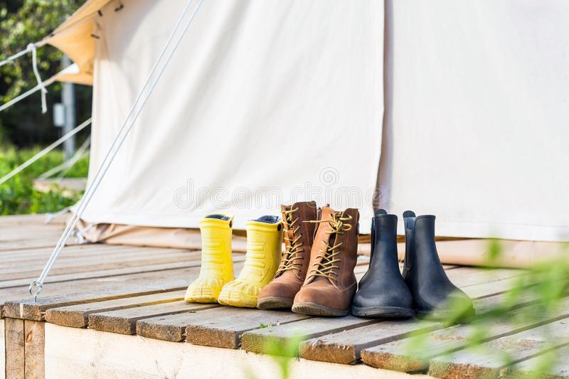 Three pair of shoes on wooden terrace behind a canvas tent royalty free stock image