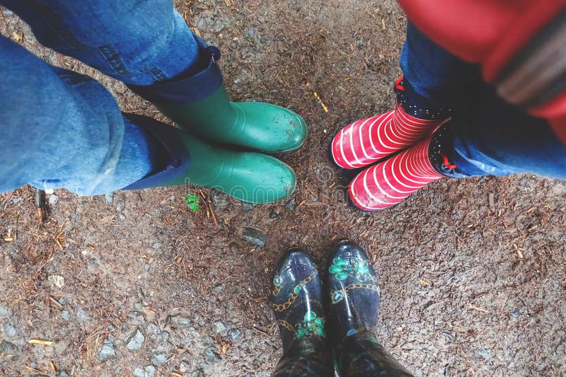 Three pairs of rubber boots at rainy autumn. View above. Three pairs of rubber boots at rainy autumn weather. View above stock photos