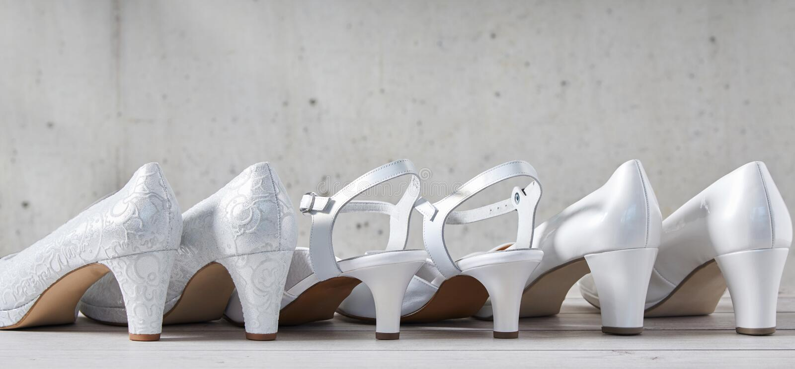 Three pairs of stylish white high heel shoes stock image