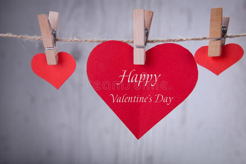 Three paper red hearts hang on destiny thread stock photography