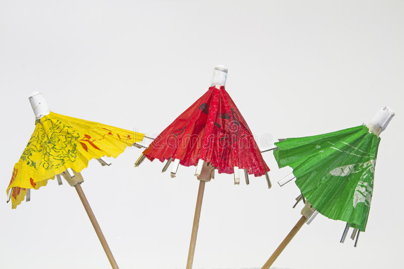 Three paper umbrellas. Colorful paper umbrellas - popular decoration for cocktails and sundaes royalty free stock photo