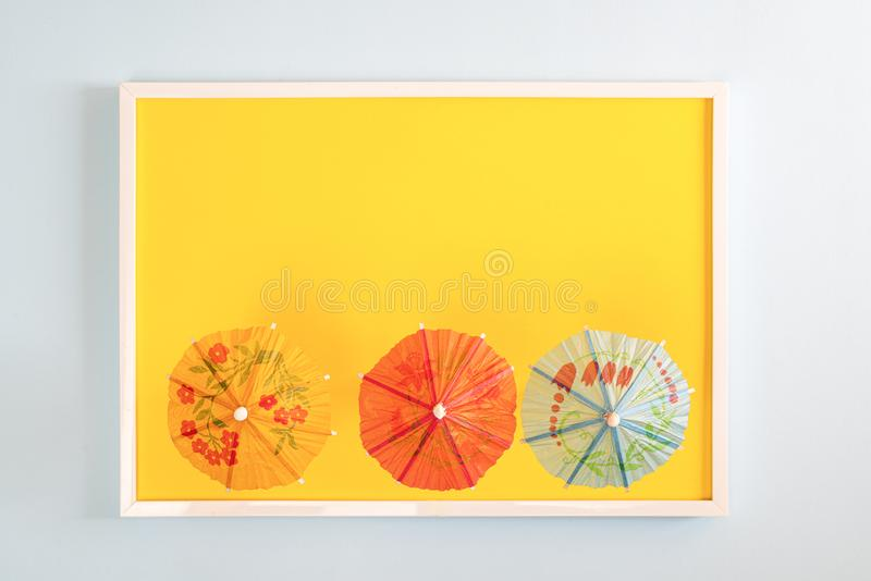 Three paper umbrellas. Three small japanese paper umbrellas in a white frame on a colored surface royalty free stock photography