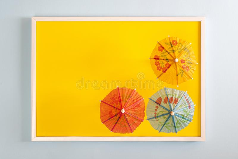 Three paper umbrellas. Three small japanese paper umbrellas in a white frame on a colored surface royalty free stock images