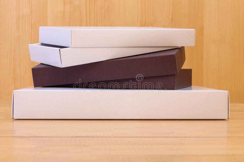 Three parted cardboard boxes stacked on top of each other. On a wooden background royalty free stock photography