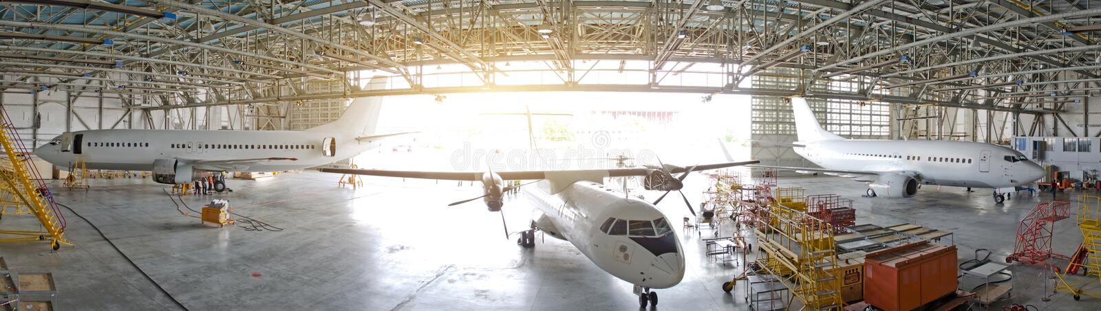 Three passenger aircraft in a hangar with an open gate for service, view of the panorama. royalty free stock photos