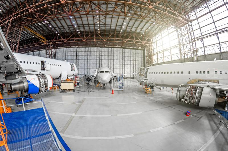 Three passenger aircraft on maintenance of engine and fuselage repair in airport hangar. Three passenger aircraft on maintenance of engine and fuselage repair royalty free stock image
