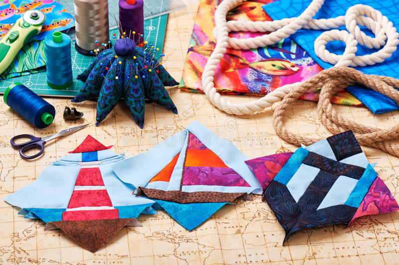 Three patchwork blocks lighthouse, yacht and anchor, fabrics, quilting tools and accessories stock image
