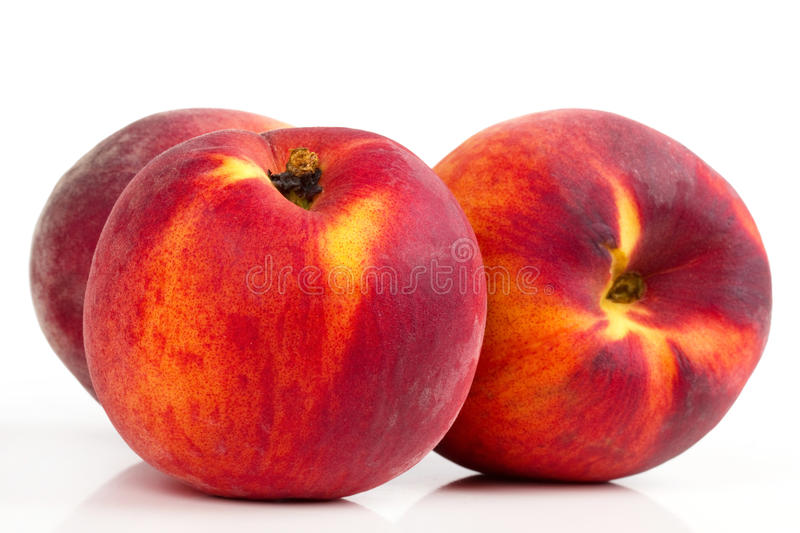 Three peaches on white table stock images