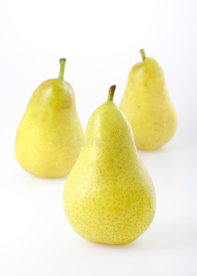 Three pears. Three yellowgreen pears on bright background. Focus on front pear stock photo
