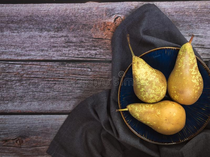 Three pears, Conference variety, on blue dish on wooden background with copy space. Fruit and harvest, food theme stock image