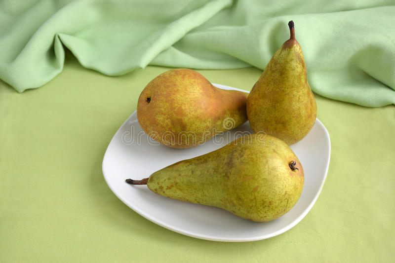 Three pears on the plate stock photography