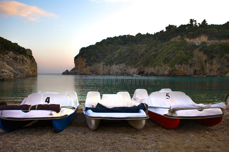 Three Pedal Boats with Folded Canopy Lining Up along the Shore. Two Cliffs Standing near the Beachfront. Coarse Sand and stock images